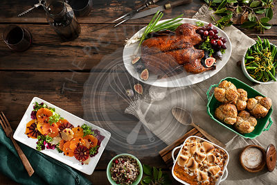 An overhead view of a holiday dinner with roasted duck, citrus salad, rice, green beans, rolls, sweet potato casserole and wi...