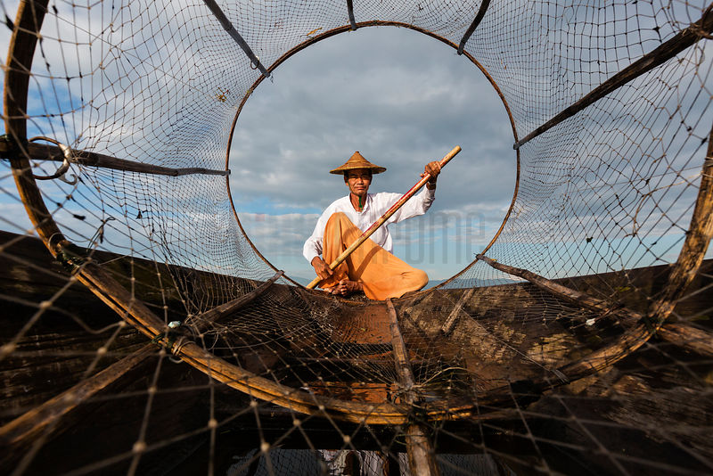 Portrait of a Traditional Net Fisherman Paddling his Boat