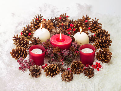 Christmas candles with pine cones in the snow