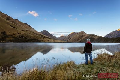 Hiker near lake at sunrise, Otago, New Zealand