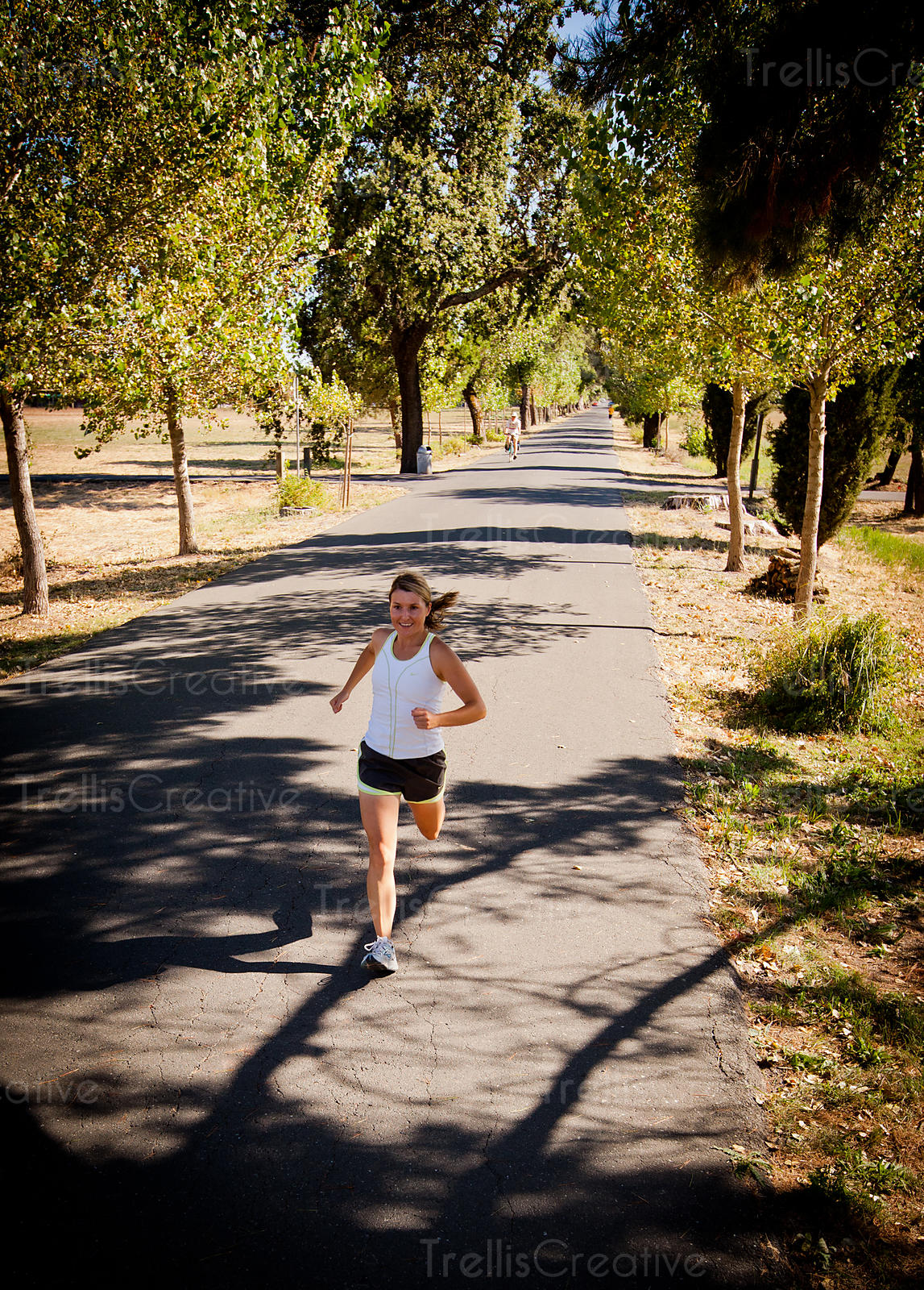 Young female runner jogging down a tree-lined street