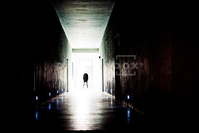 An atmospheric image of a blurred figure of a man standing at the end of a dark corridor.