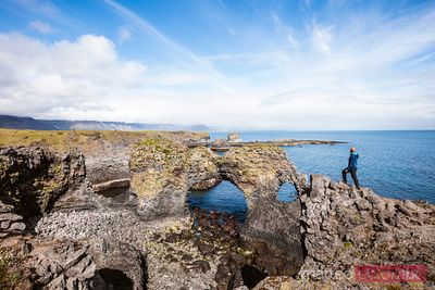 Man near natural rocky arch, Snaefellsnes peninsula, Iceland