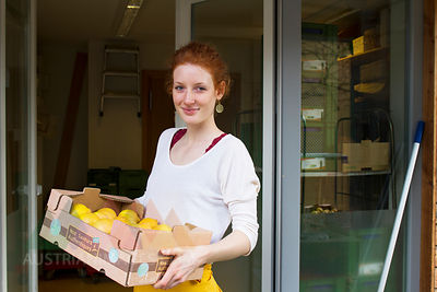 Portrait of smiling young woman with cardboard box of lemons in front of wholefood shop