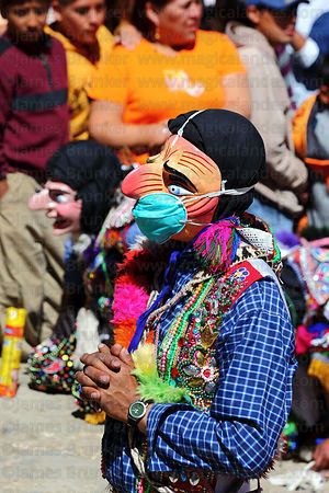 Masked Maqtas dancer wearing swine flu mask kneeling outside church during mass at Virgen del Carmen festival , Paucartambo ,...