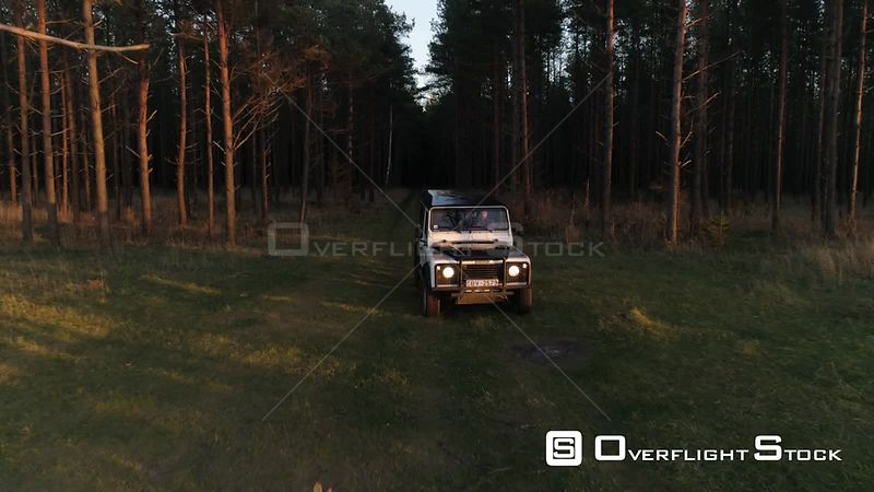 Aerial drone tracking shot of vintage 4x4 off road vehicle driving in forest towards sea Latvia