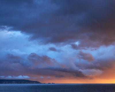 Dramatic sunset storm lighting and clouds over The Needles on the Isle of Wight, viewed form the clifftop at Milford-on-Sea, ...