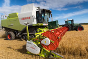 Claas Lexicon 760 combine filling trailer with grain, pulled by a Fendt Vario 820 at harvest time, North Yorkshire, UK.
