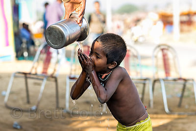 A boy drinks from a metal water pot at the Pushkar Camel Fair, Pushkar, Rajasthan, India