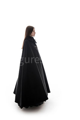 A woman in a big cloak standing and looking away – shot from eye level.