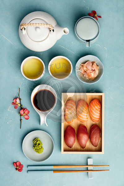Nigiri sushi with salmon and tuna served on bamboo plate on blue background