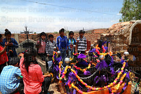 Children saying prayers for souls of the dead next to grave during Todos Santos festival, Sipe Sipe, Cochabamba Department, B...