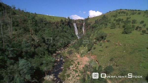 Aerial shot over a lush green river canyon towards some waterfall then over a rocky river Sabie. Mpumalanga South Africa