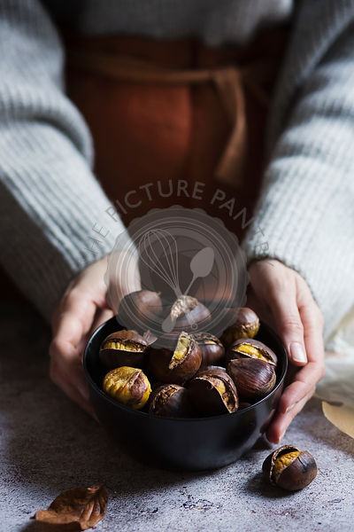 Woman holding a bowl with roasted chestnuts