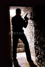 An atmospheric image of the silhouette of a mystery man with a gun at the bottom of some cellar steps.