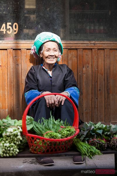 Old chinese Zhuang minority  woman selling vegetables