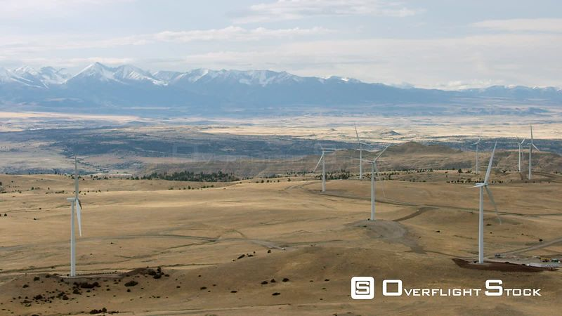 Golden plains sit in the shadow of the snow-capped Beartooth mountain Range in southwestern Montana. A group of wind turbines...