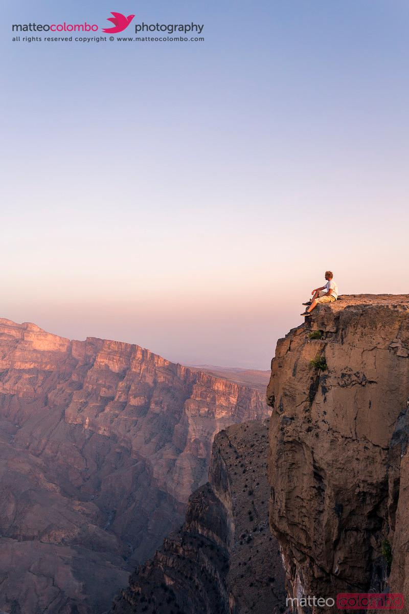 Man sitting on the edge of cliff, Jebel Shams, Oman