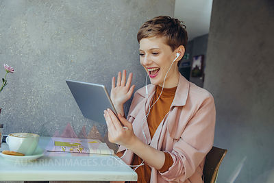 Woman with tablet waving to somebody during a video conference in a cafe