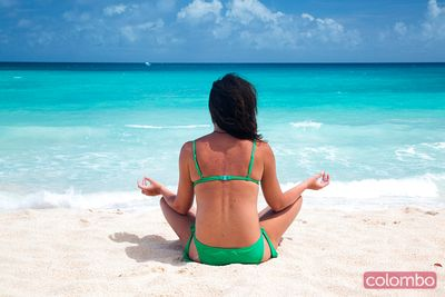 Woman in lotus position doing yoga on tropical beach