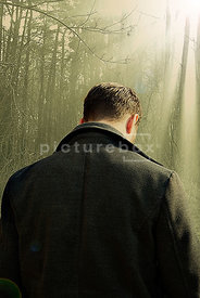 An atmospheric image of a mystery man from behind, looking down, in a sunlit forest.
