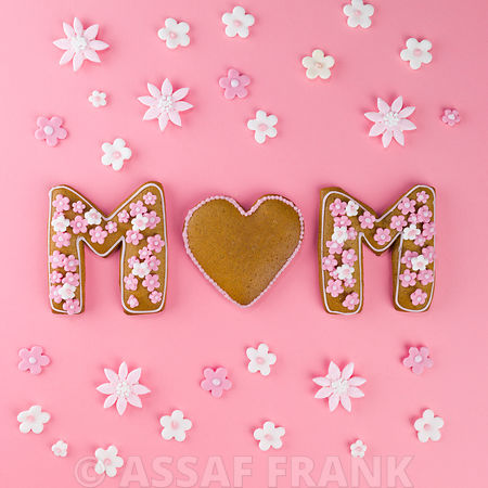 Word MUM of gingerbread cookie on pink background