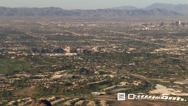 Flight past outlying areas and rocky peak to reveal Phoenix in distance.