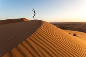 Oman, Wahiba Sands. Tourist jumping on the sand dunes