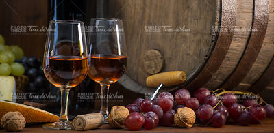 Glasses of rose wine cheeses grapesand barrel on brown wooden background