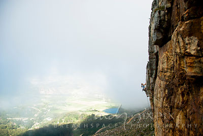 A female rock climber high on a steep vertical cliff, with mist behind just revealing the ground below.