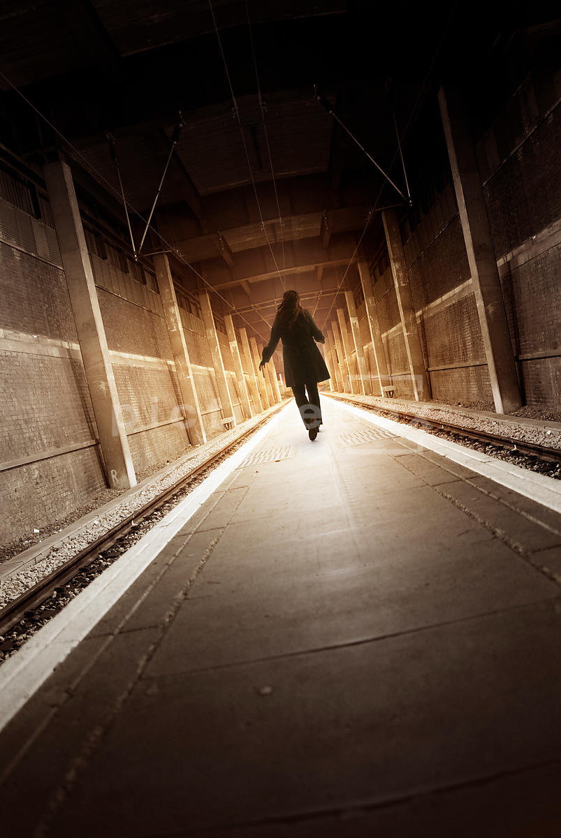 An atmospheric image of a mystery woman walking down an empty train platform In London, England.
