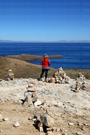 Tourist looking at view from summit of Cerro Thikani at northern end of Sun Island, Lake Titicaca, Bolivia