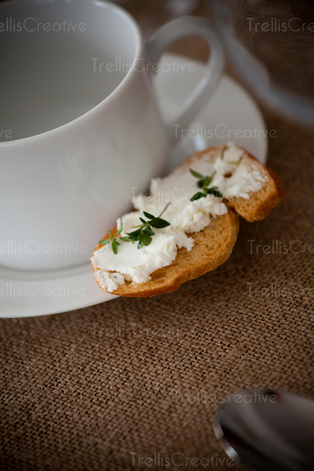 Empty white cup and crustini with goat cheese