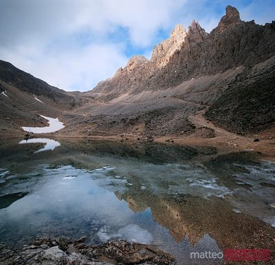 King Laurino peaks reflected in small alpine lake in the Dolomites Italy