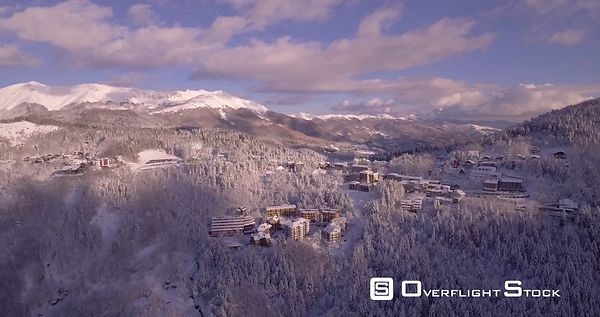 Aerial, beautiful woods under the snow and the view on the snowy mountains with little villages in winter