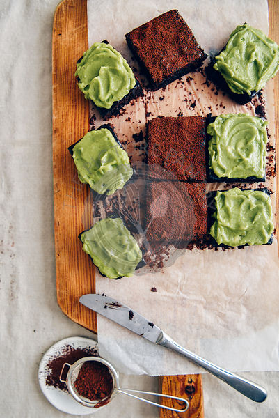 Avocado brownies some of which are topped with avocado frosting and the rest of which are topped with cocoa powder photograph...