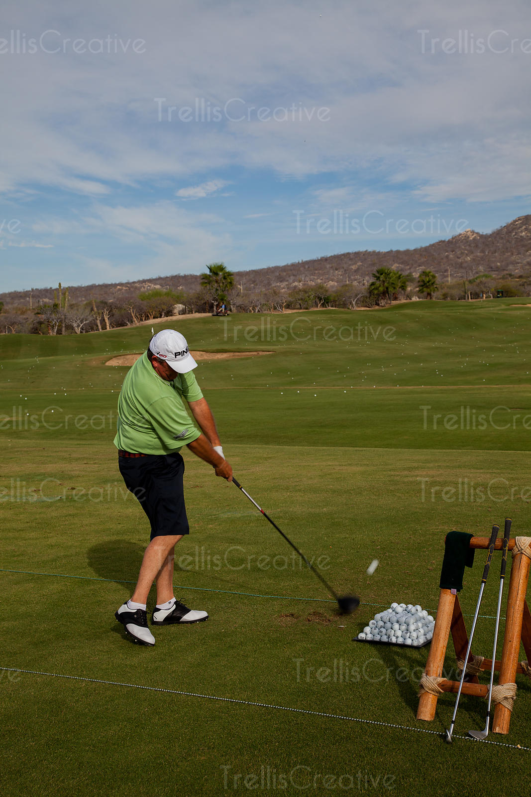 A golfer practicing his drive at a golf driving range