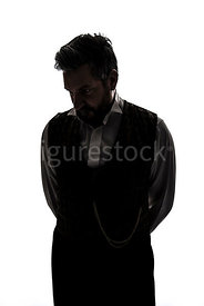 A Victorian man in a waistcoat, looking down, in semi-silhouette – shot from eye level.
