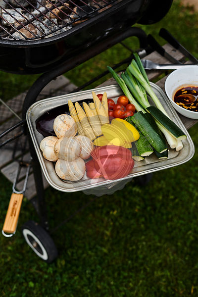 Overhead view of tray of colorful raw vegetables on side of barbecue waiting to be grilled