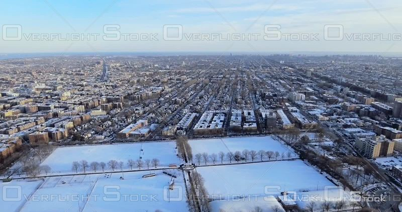 Aerial Over Snow Covered Football Fields and Brooklyn Brownstones and Buildings Winter NYC