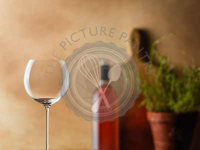 A delicate wine glass with wine and a warm kitchen setting in background.