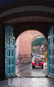 Vintage car in doorway of church in Cusco, Peru ready to drive away bride and groom.