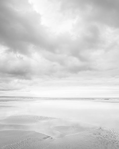 Cloud formations and wet sand on the vast expanse of beach at Sandymouth, Bude, Cornwall, UK
