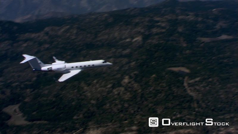 Air-to-air orbiting view of business jet over rugged terrain
