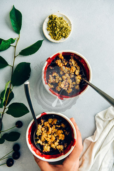 A woman holding cherry crisp with oats in a white ramekin with a spoon on the side