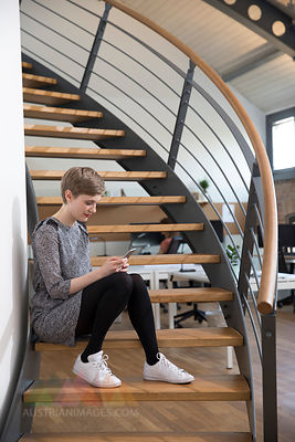 Woman sitting on stairs in modern office looking at cell phone