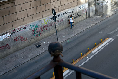 Italy - Palermo - A women walks down Via Maqueda past a wall covered in graffiti