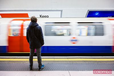 Boy standing on a underground platform with train passing