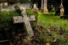 A stone cross lying against a headstone in a graveyard. (selective focus)