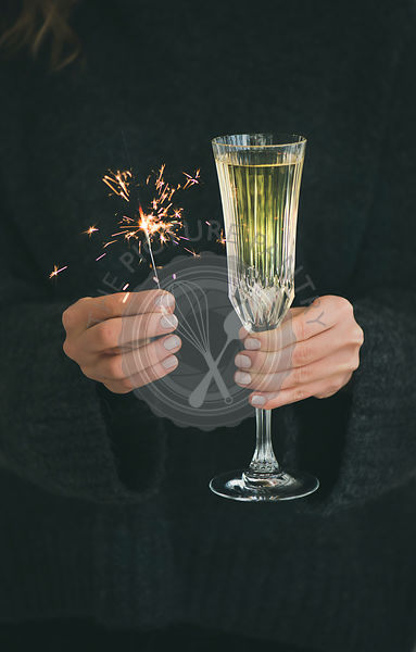 Woman in grey sweater holding Christmas sparklers and glass of champagne